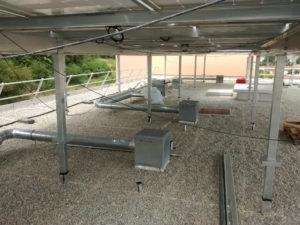 """Photographie extérieure de la résidence """"le Granoly"""". Zoom sur toit équipé d' une installation de type """"champ solaire photovoltaïque"""". Rénovation logements sociaux collectifs."""