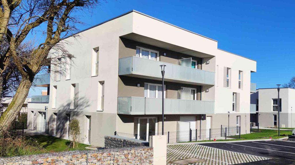 Photographie, prise en extérieure, qui représente la façade d'un immeuble neuf de logements collectifs.